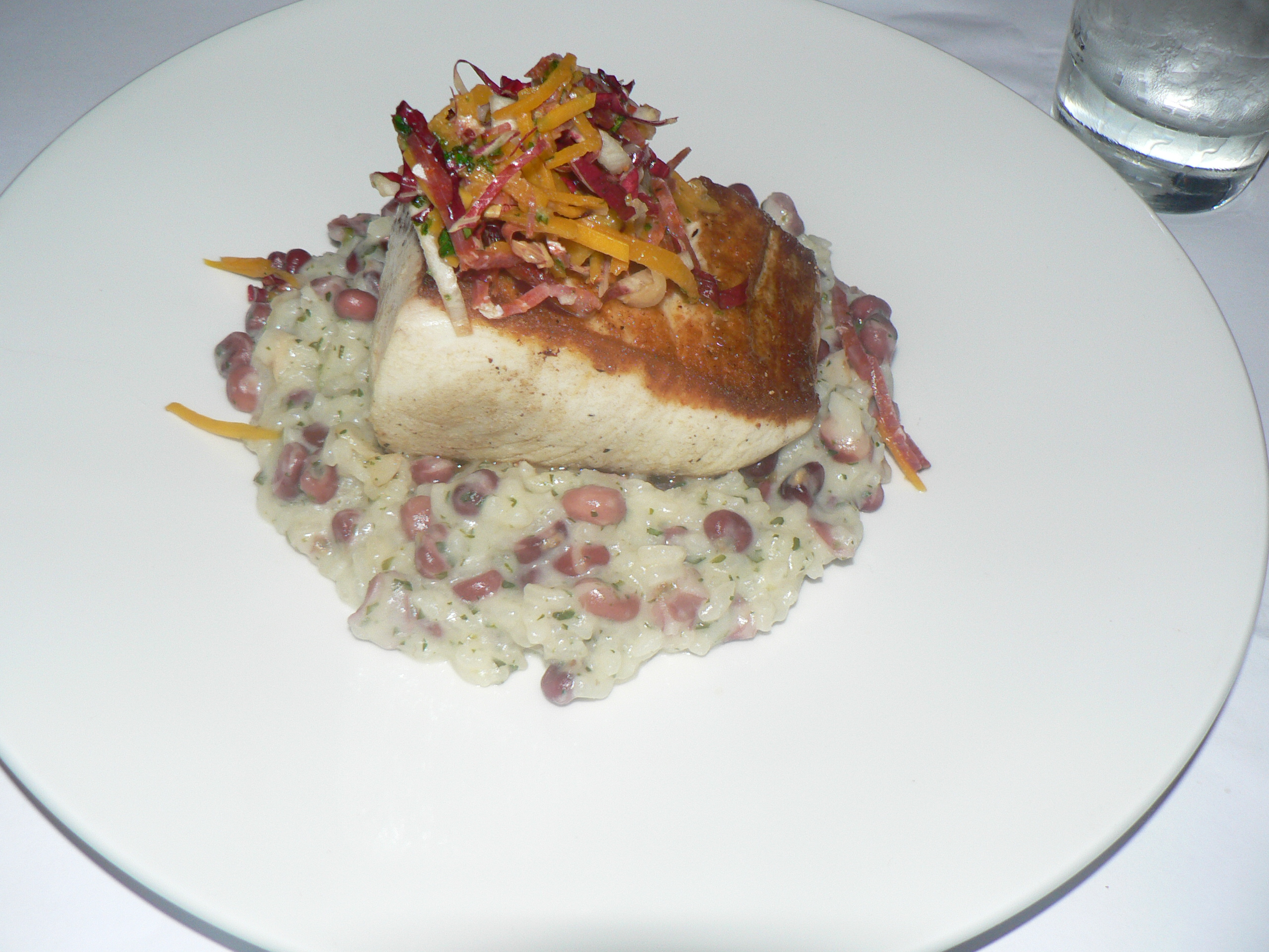 cooked wahoo on top of a bed of rice and beans with garnish