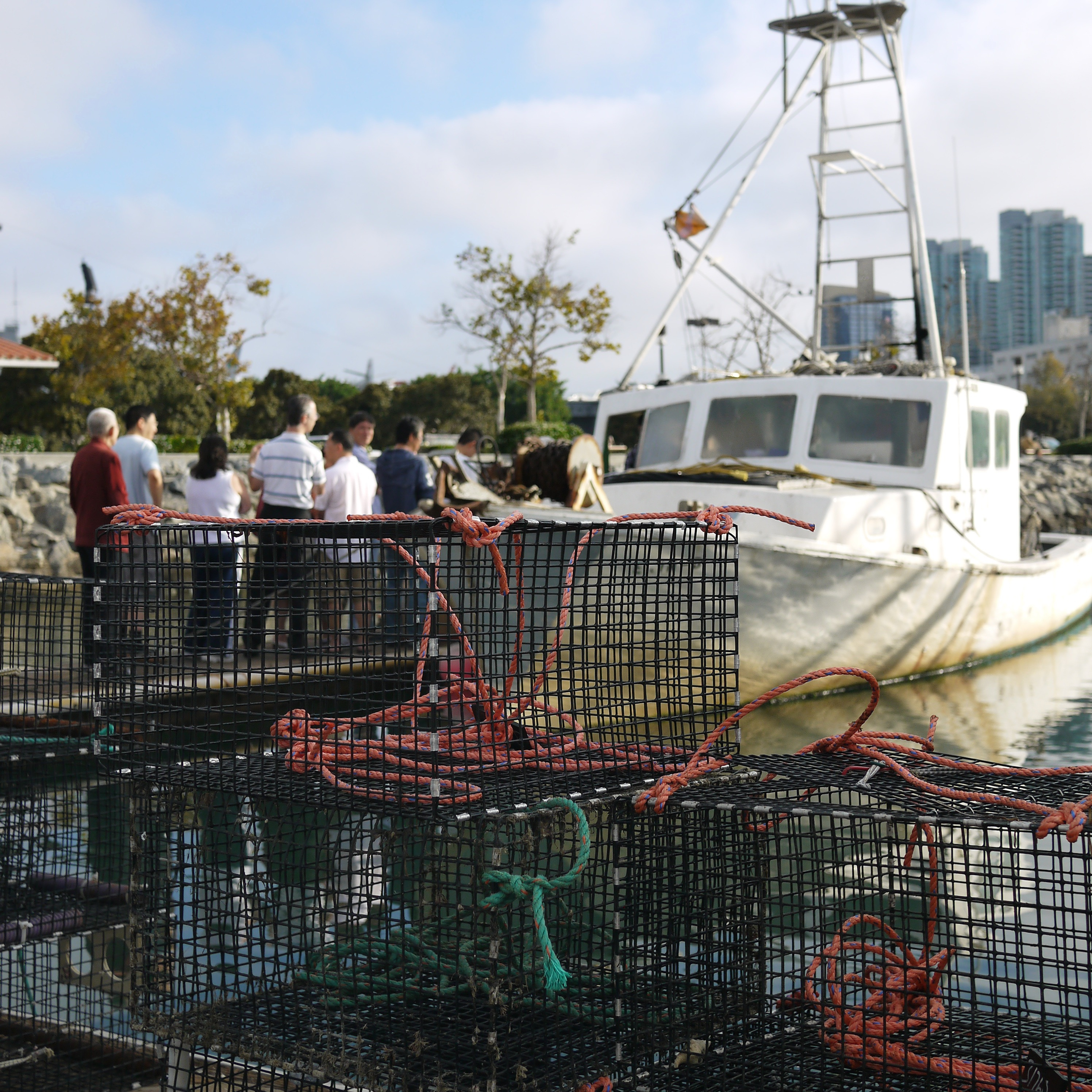 People on dock next to fishing boat with traps