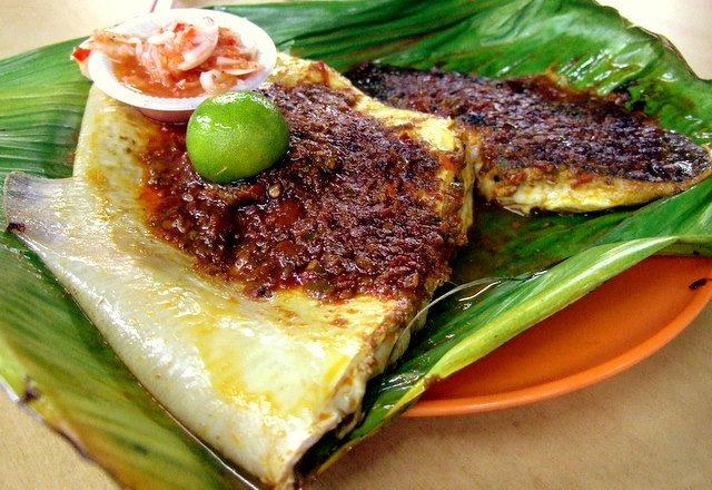cooked stingray with sambal sauce, lime, dipping sauce, on top of a banana leaf