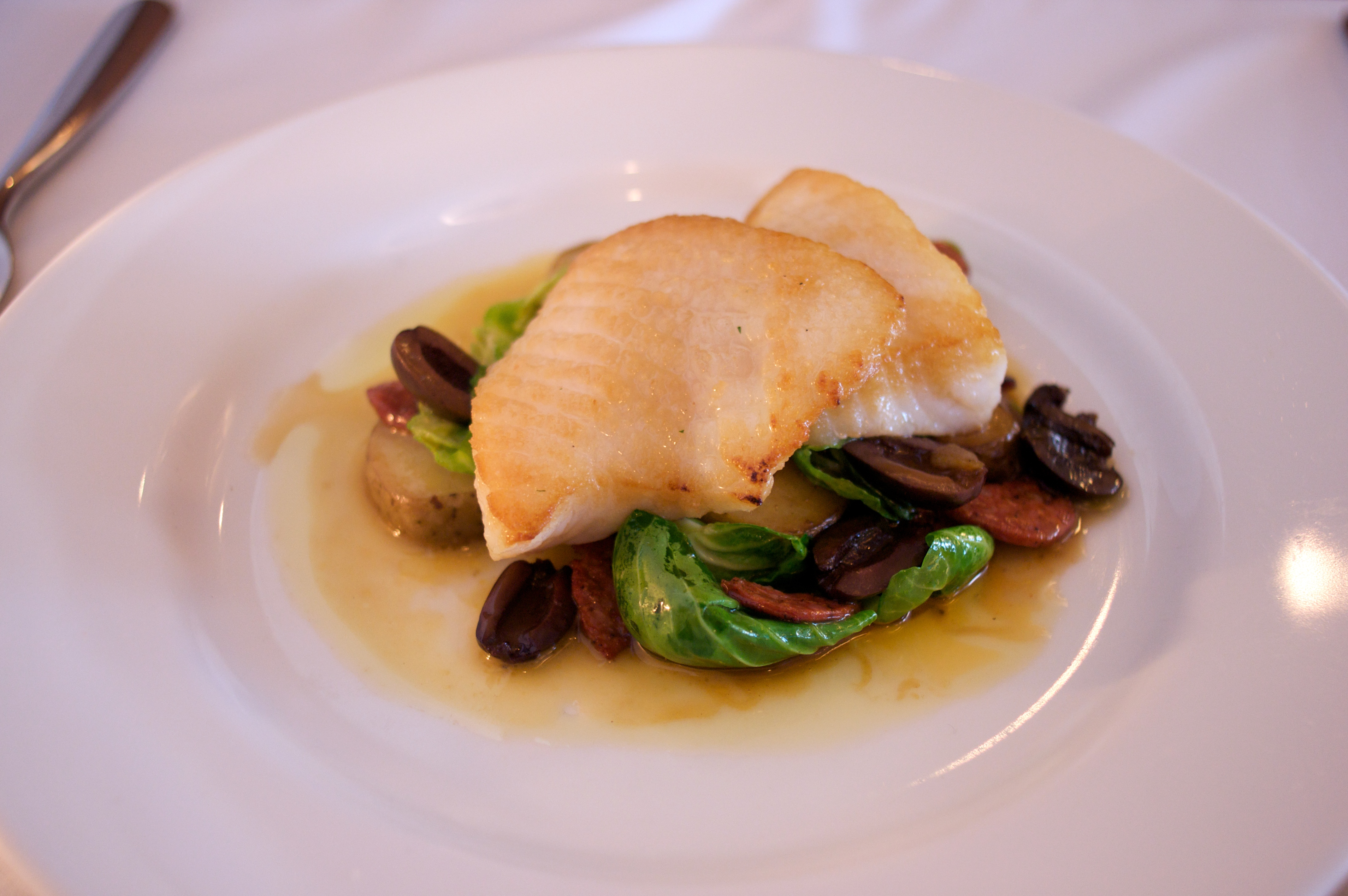 pan-seared lingcod with brussel sprout leaves, sausage, olives, and potato