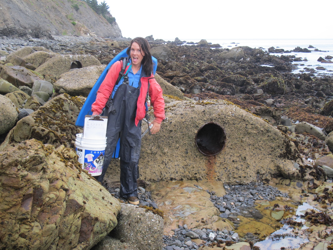 Woman standing in tidepools holding research equipment
