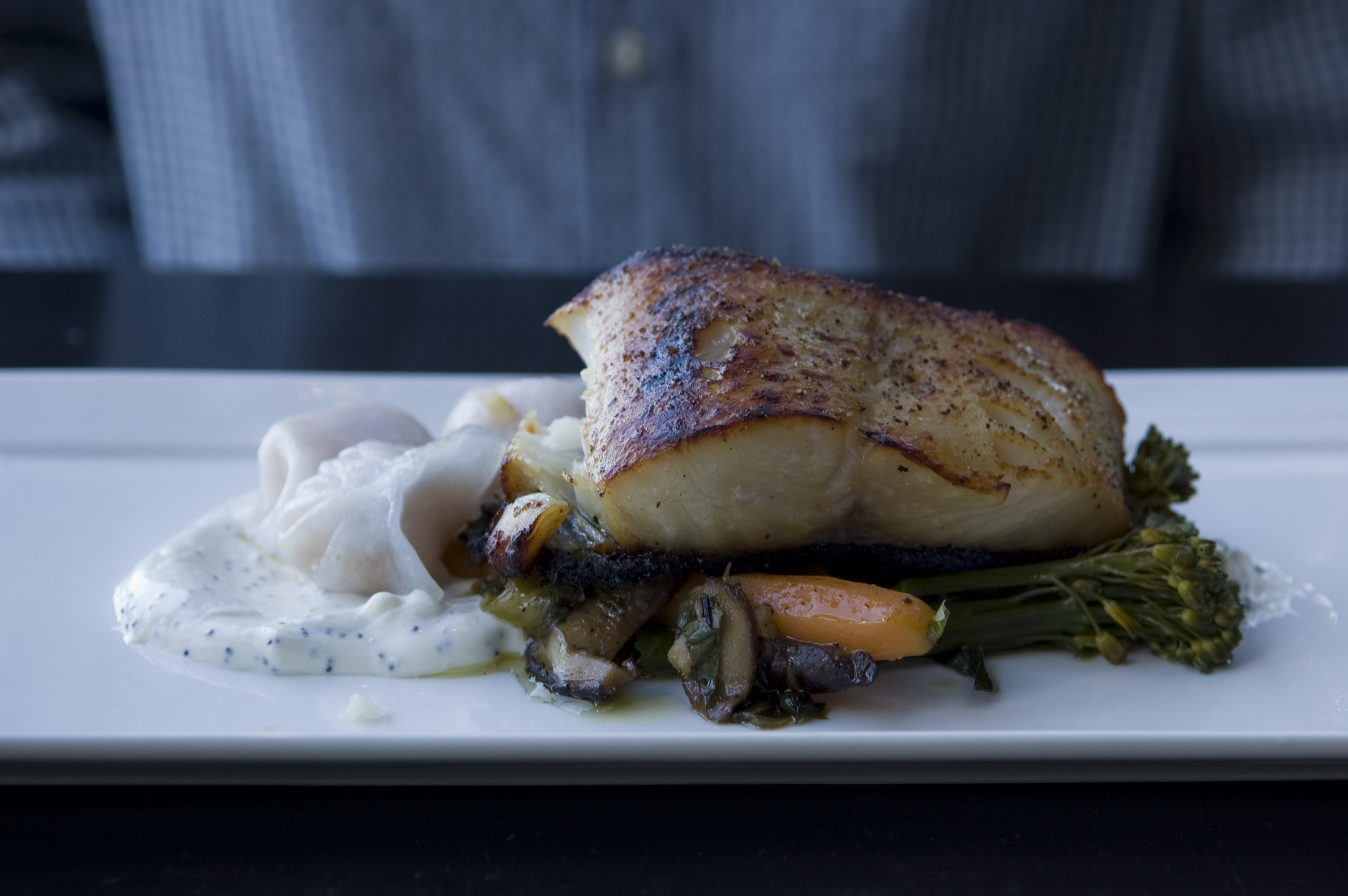 sablefish on a bed of broccolini, mushrooms, carrots, and cream sauce