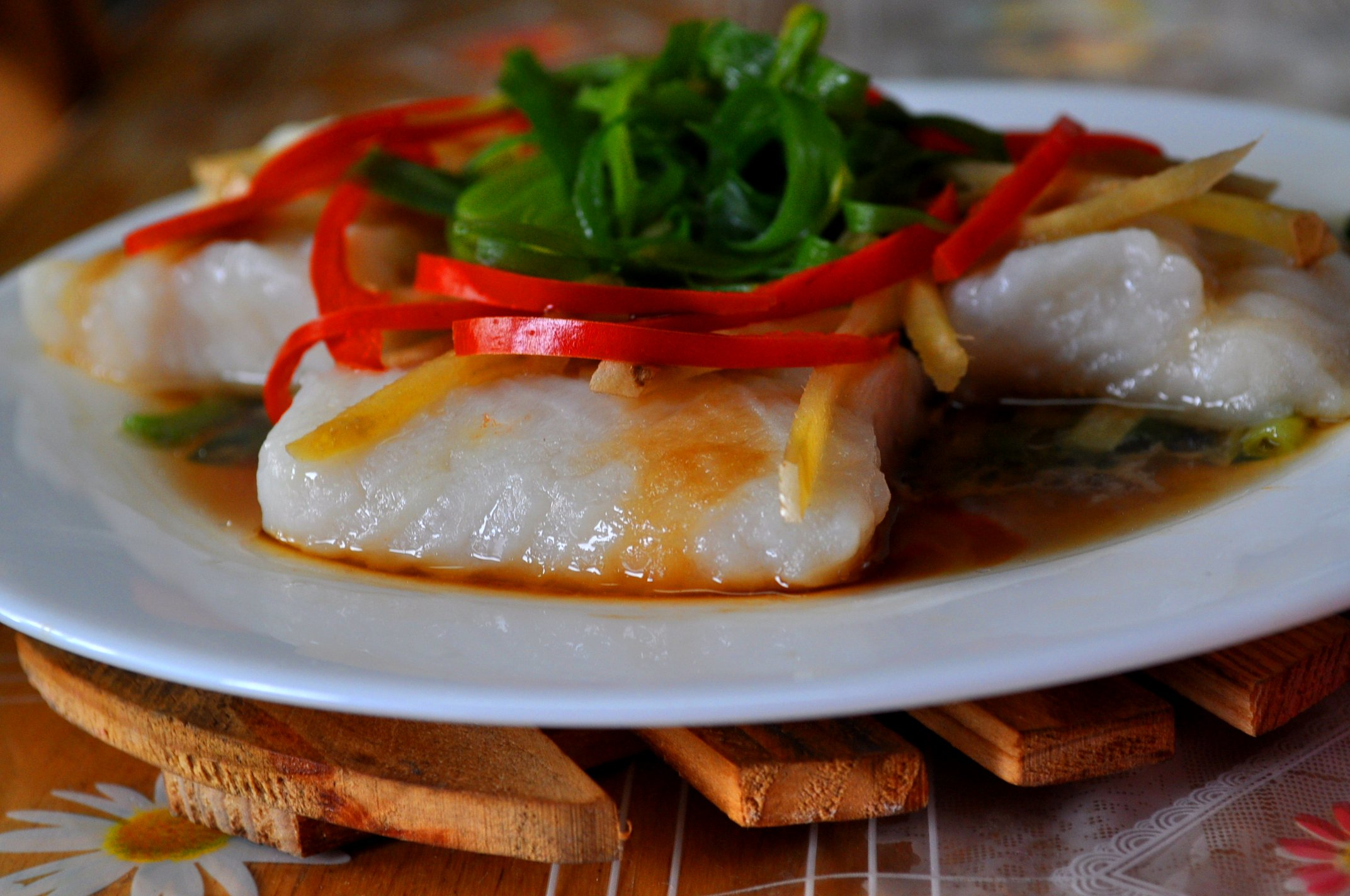 steamed fish with bell pepper and  green onion garnish and soy sauce
