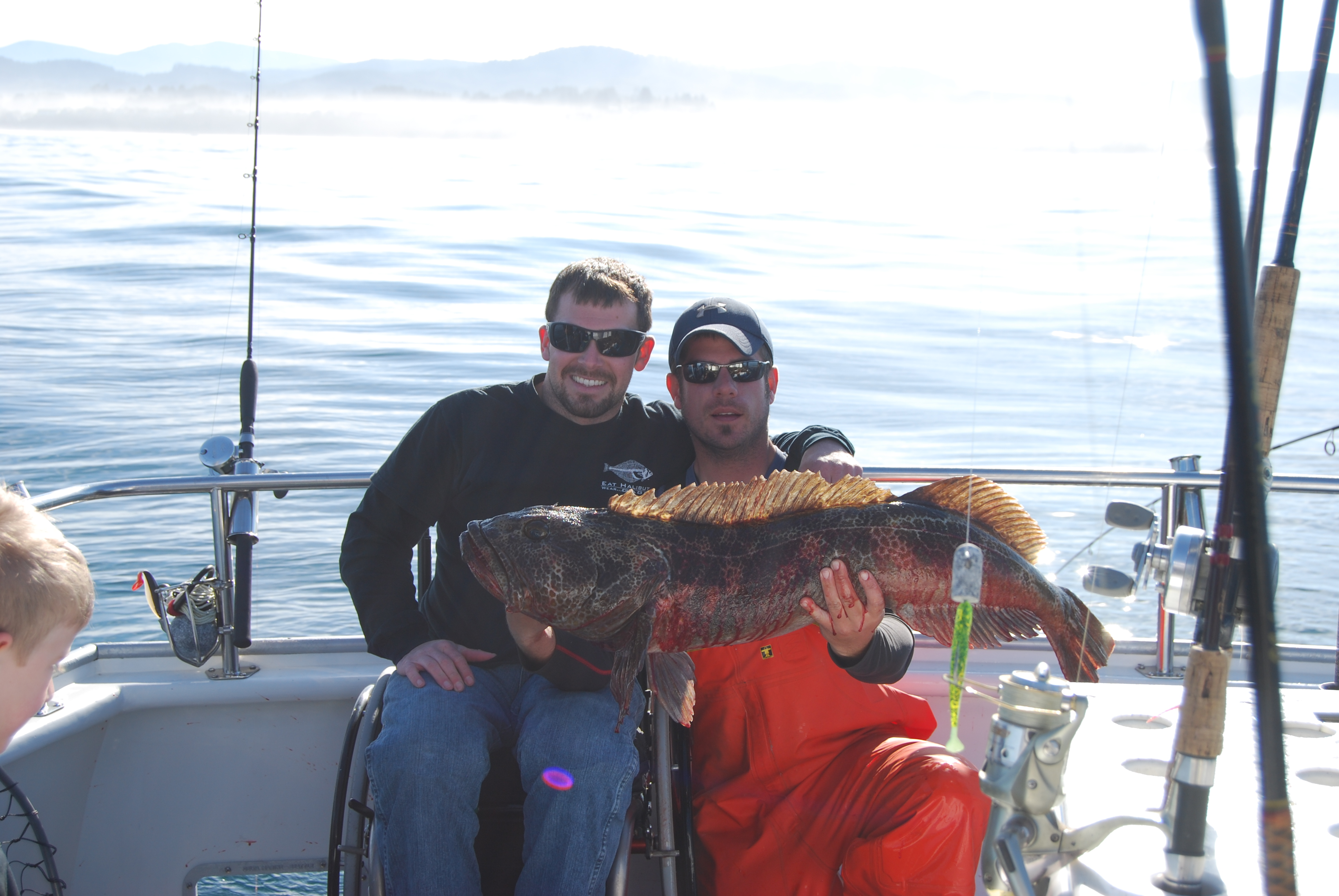 two people holding a lingcod fish aboard a fishing boat with fishing poles, one person is on a wheelchair
