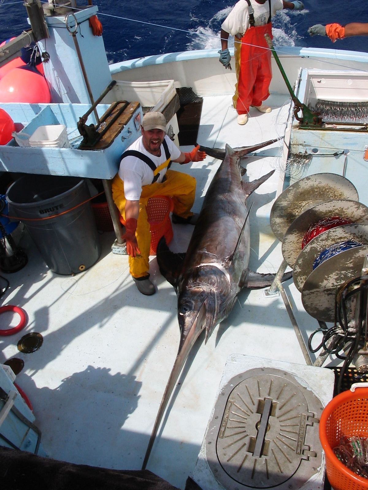 A fisherman poses with a swordfish on boat deck