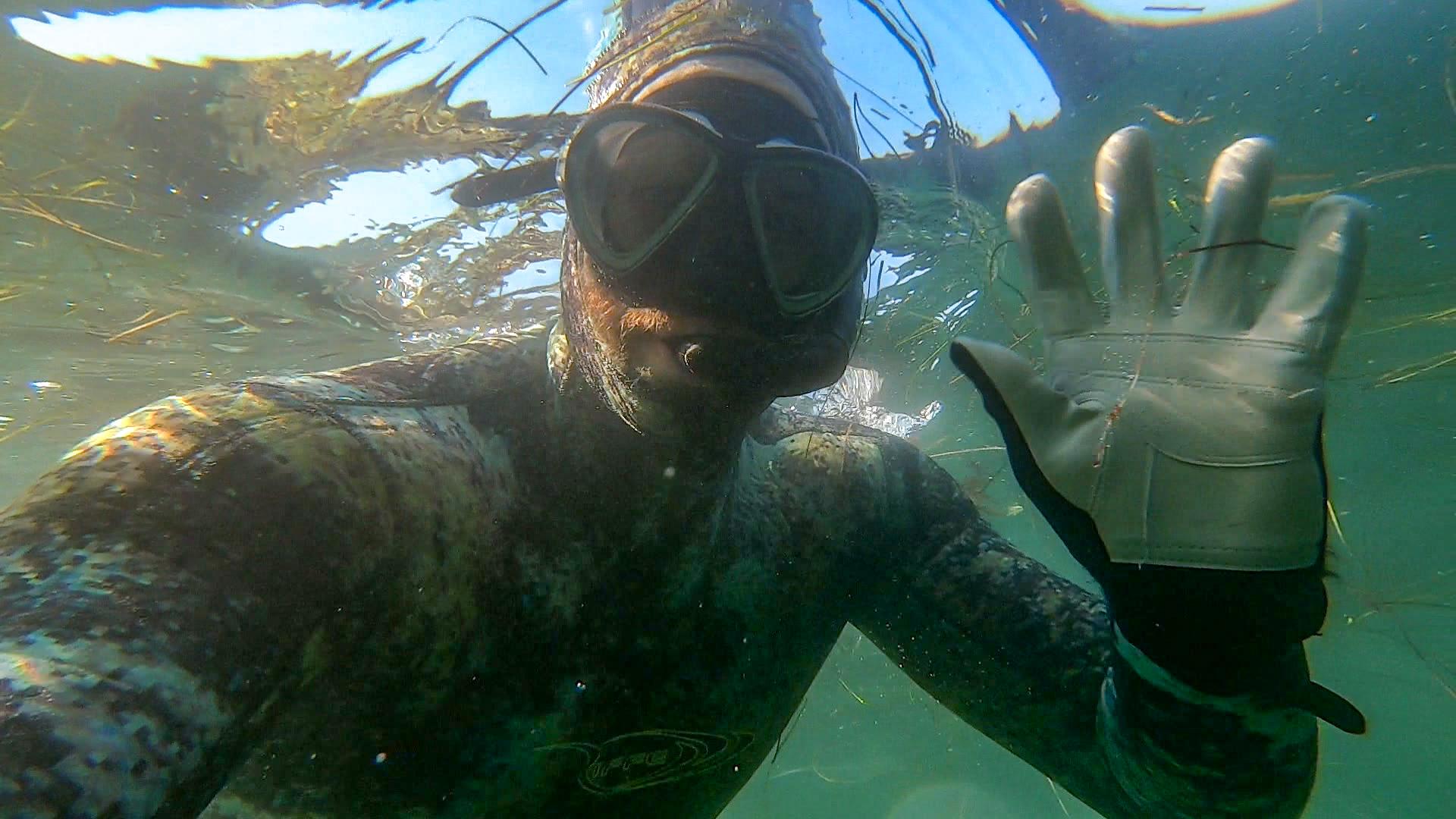 snorkeler waving at camera underwater