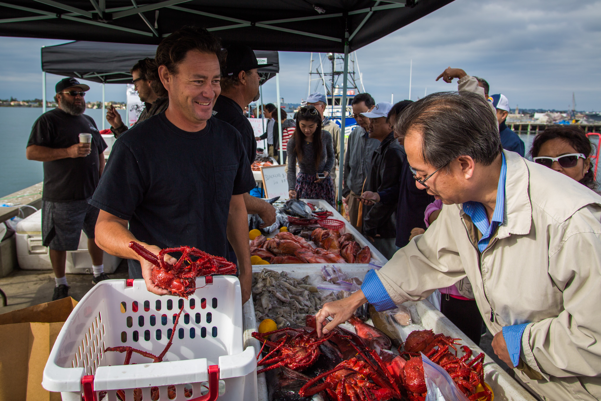 fisherman selling red king crab to a customer