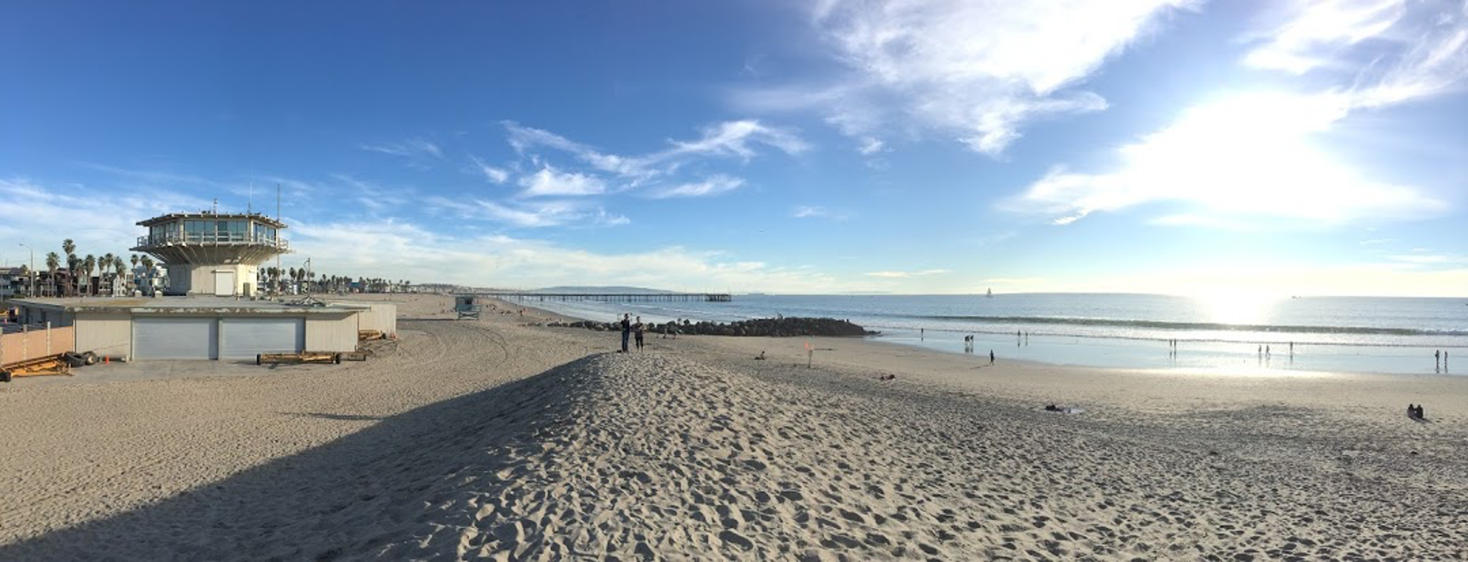 Panorama of a sand berm on Venice beach and lifeguard tower