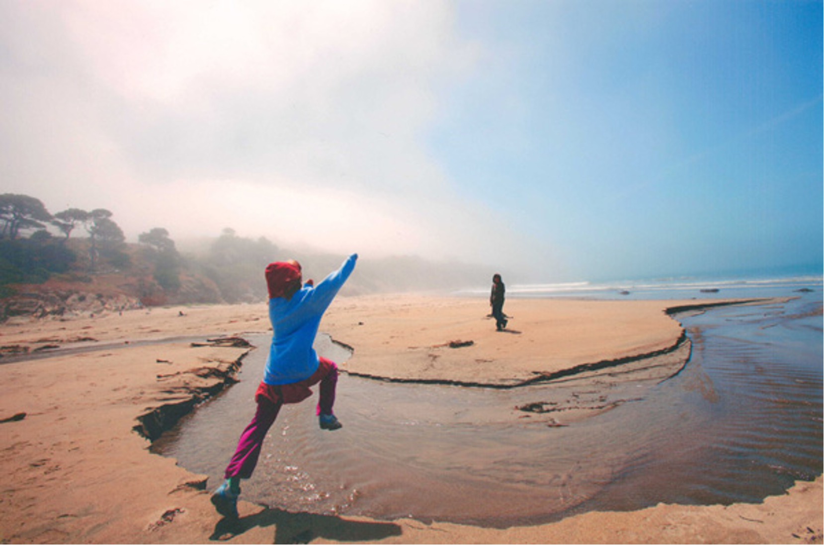 child jumping over a stream of water flowing through a beach