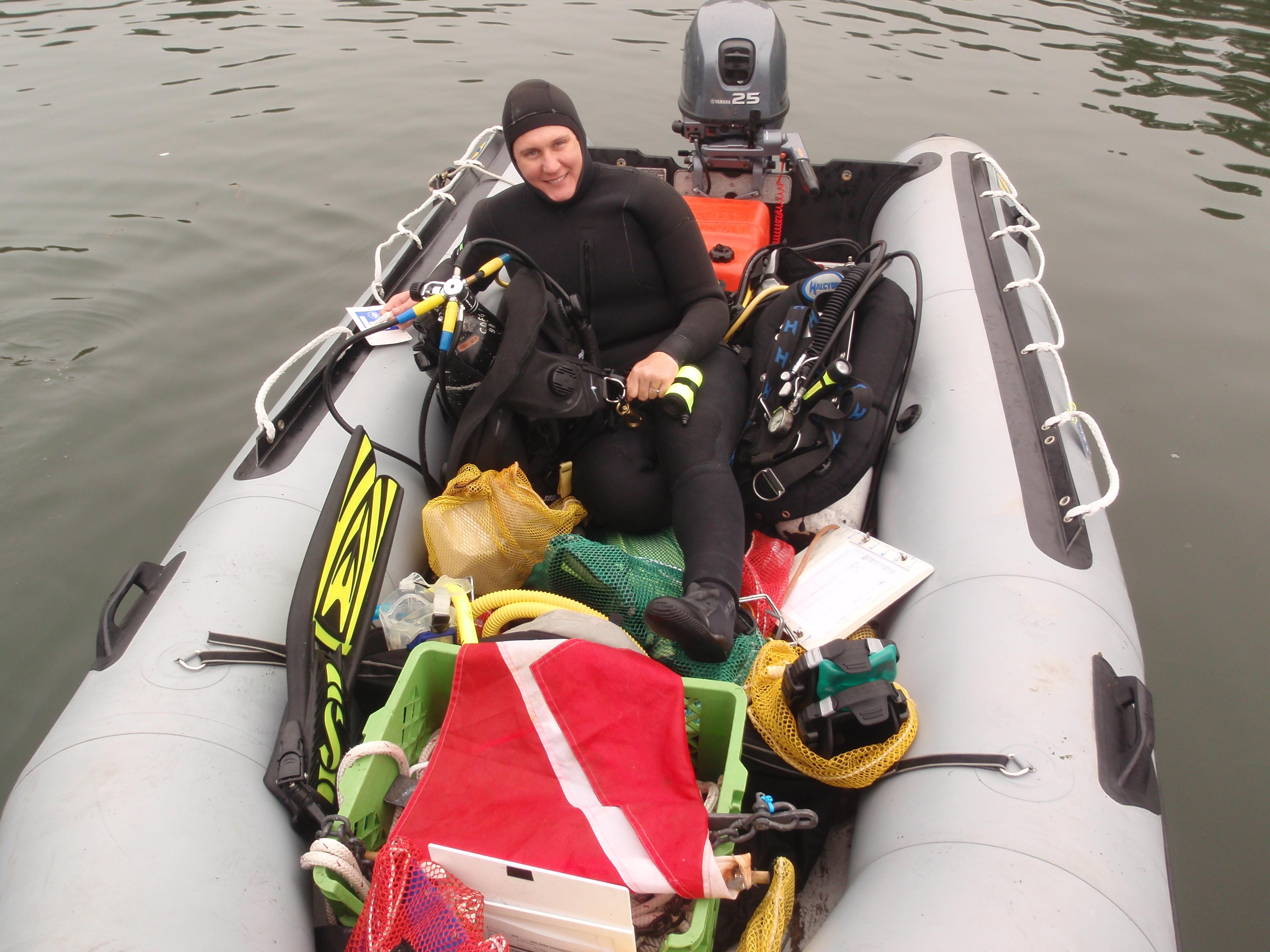Researcher siting in boat full of scuba dive gear