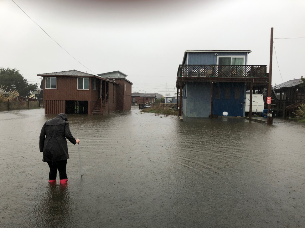 Woman measuring floodwaters next to houses