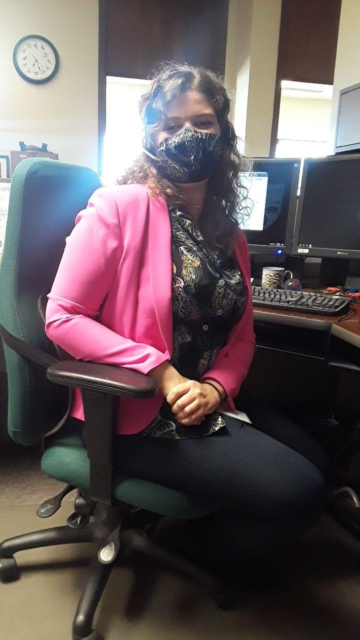 Rose Dodgen, sitting at her office desk wearing a face mask