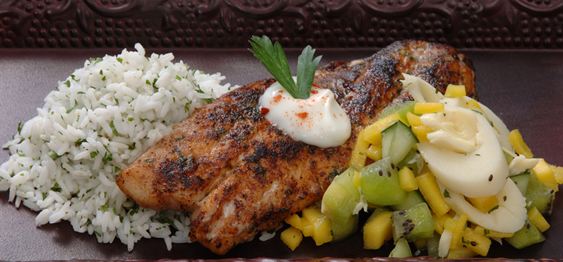 Cooked fish filet with vegetables, rice, and garnish