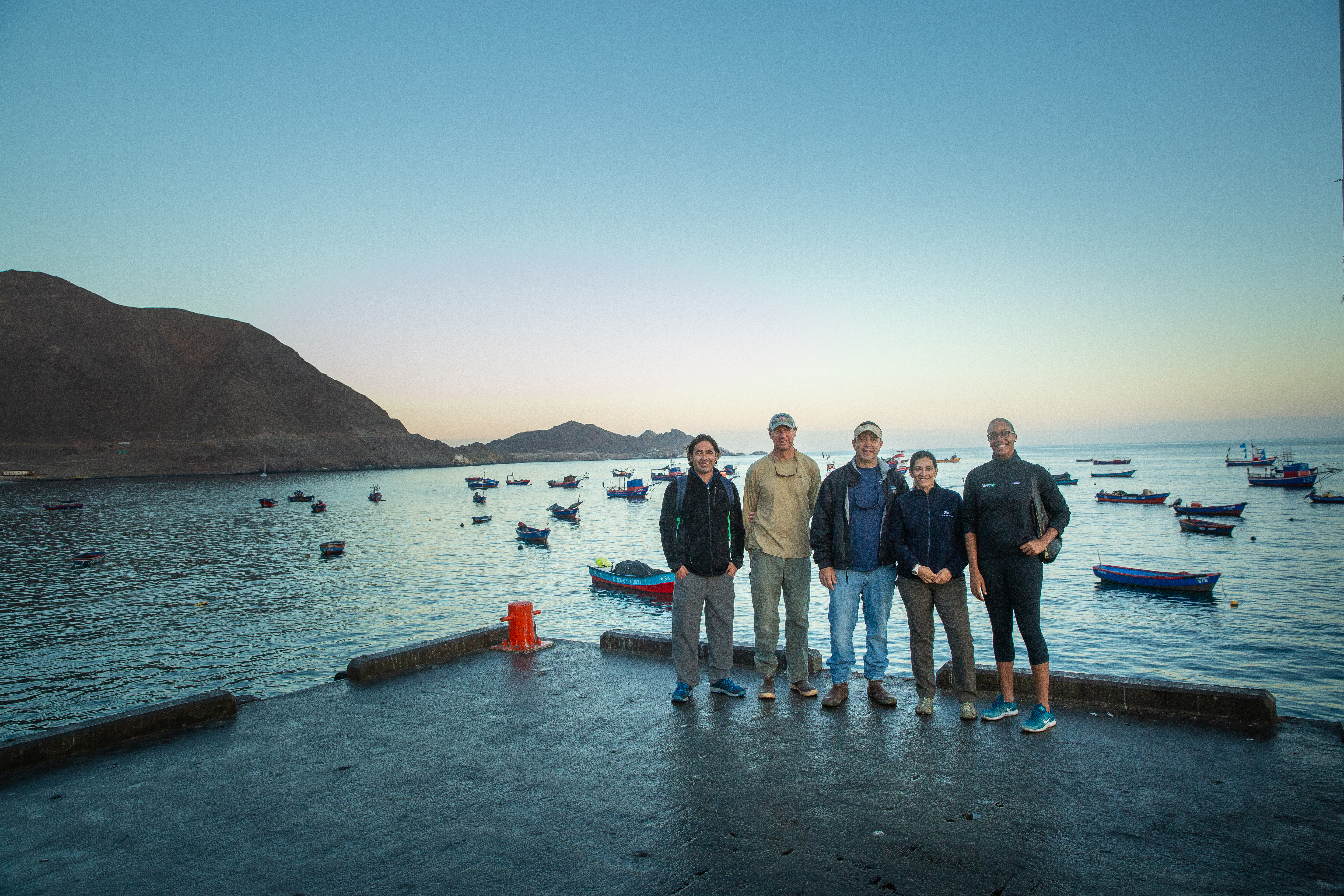 five people standing on a dock in Chile, with small boats behind them