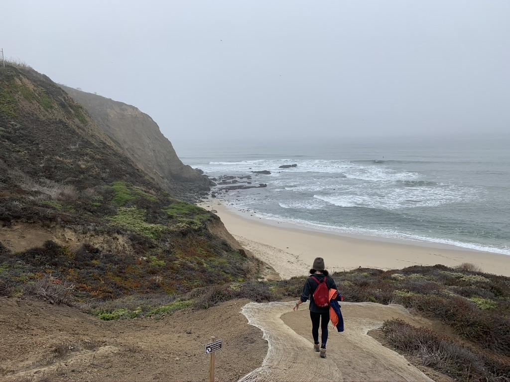Woman walking down a trail toward the beach