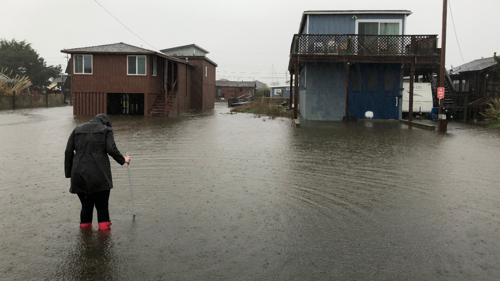 Woman measuring flood waters by houses