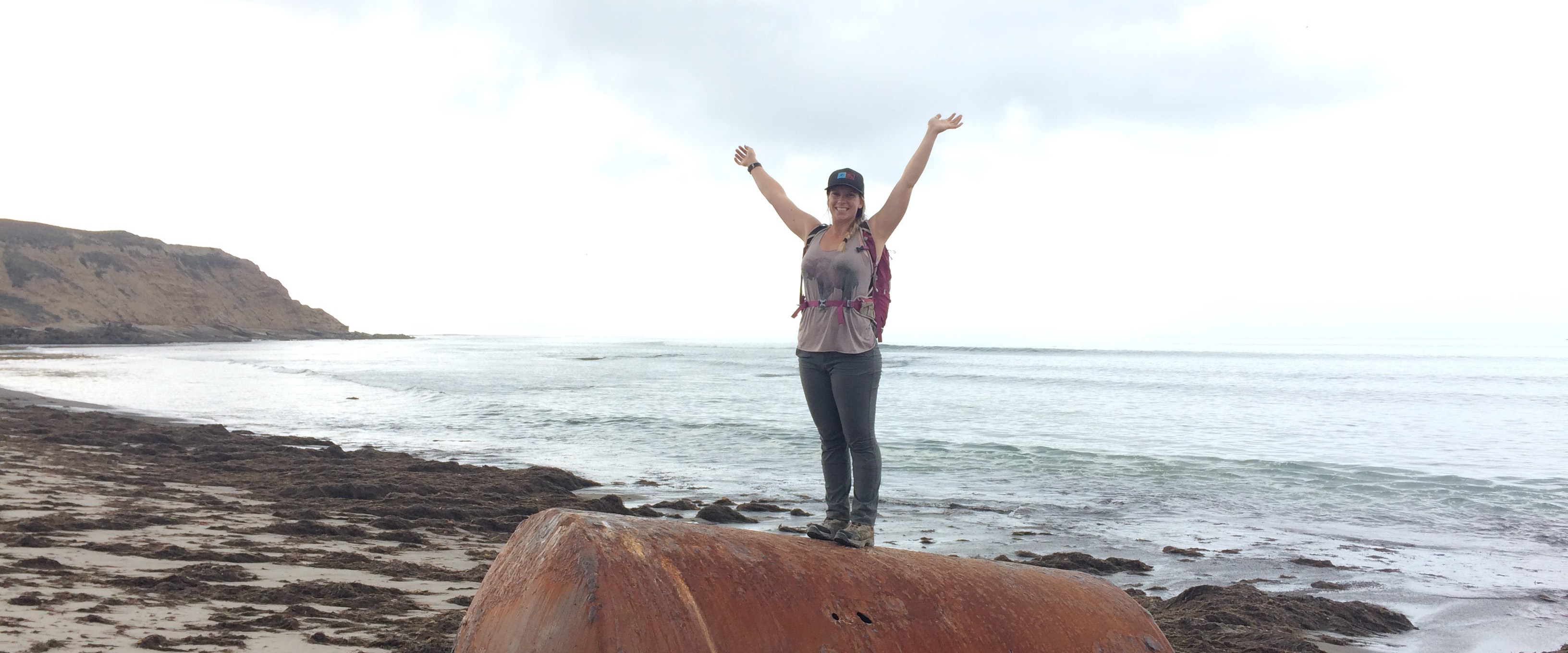 Michaela standing on a large metal drum on a beach