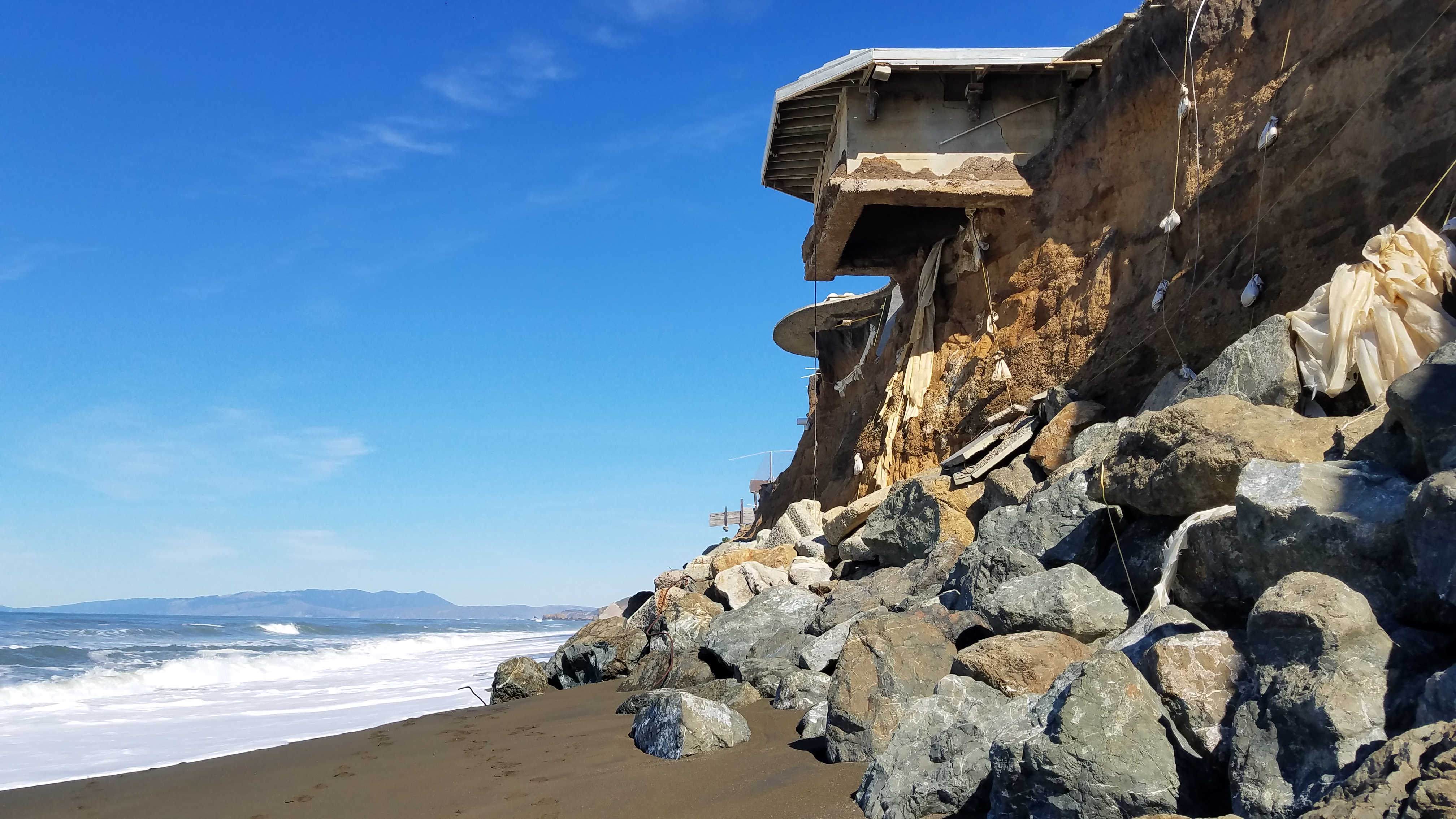 "An example of coastal erosion and a type of ""gray"" shoreline armoring structure called a revetment in Pacifica, CA.  Foundations of former homes are becoming exposed at the top of the bluff. Photo credit: Karen Vu"