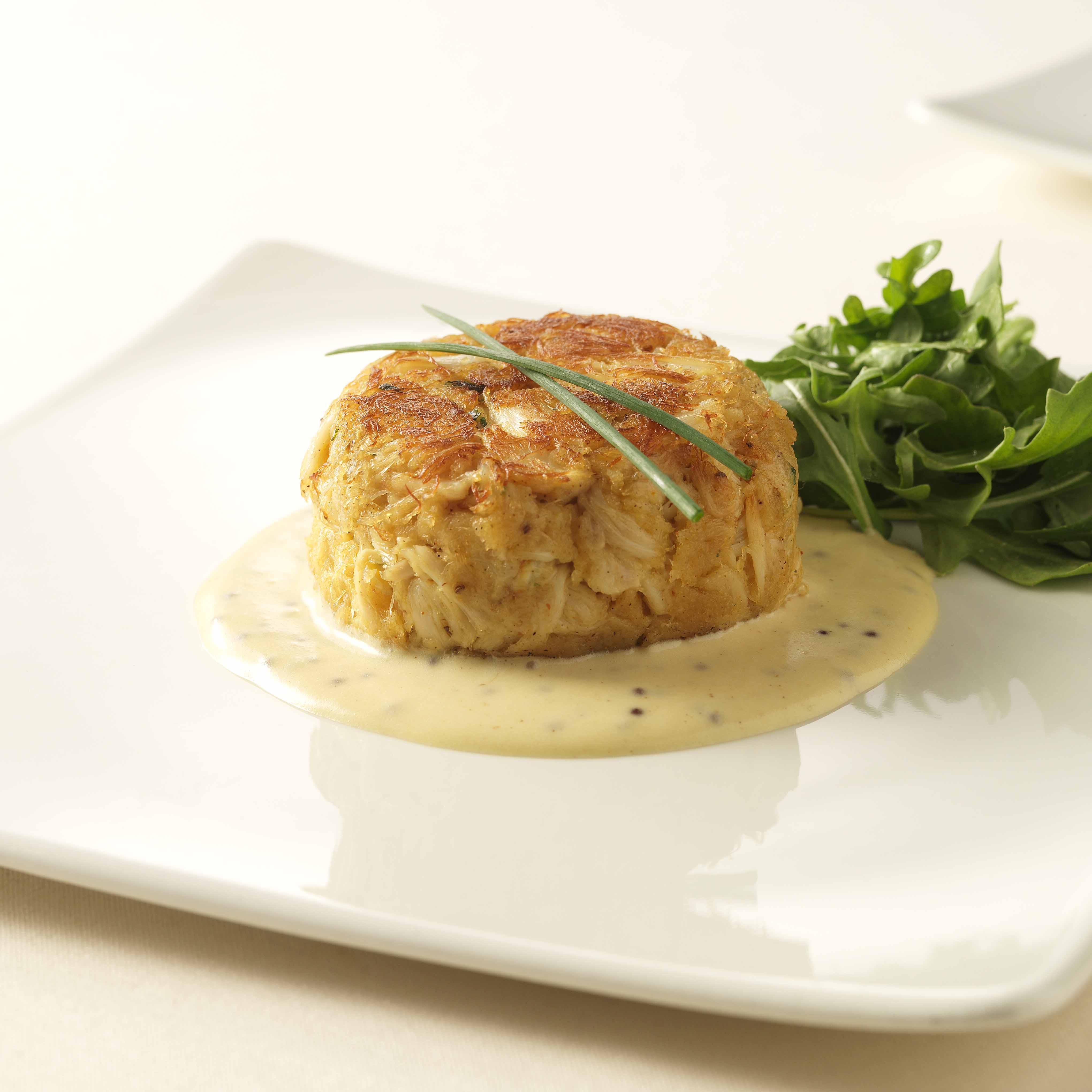 crab cake on top of yellow cream sauce, garnished with salad greens and green onion