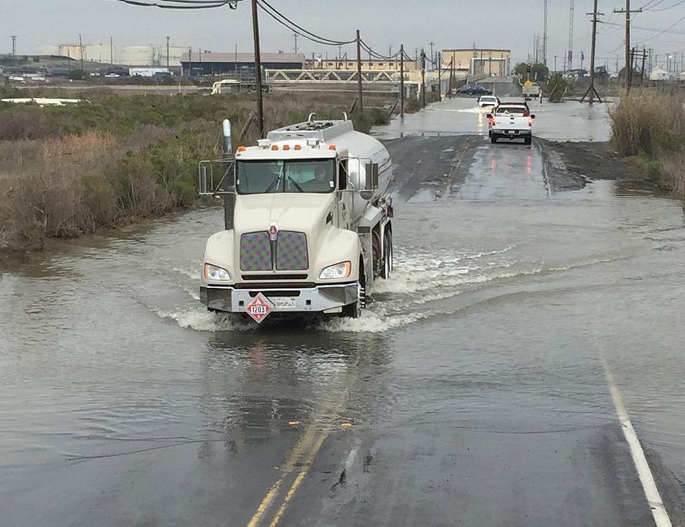 trucks driving through flooded street