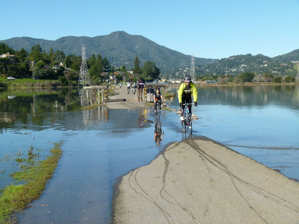 cyclists riding across a flooded path
