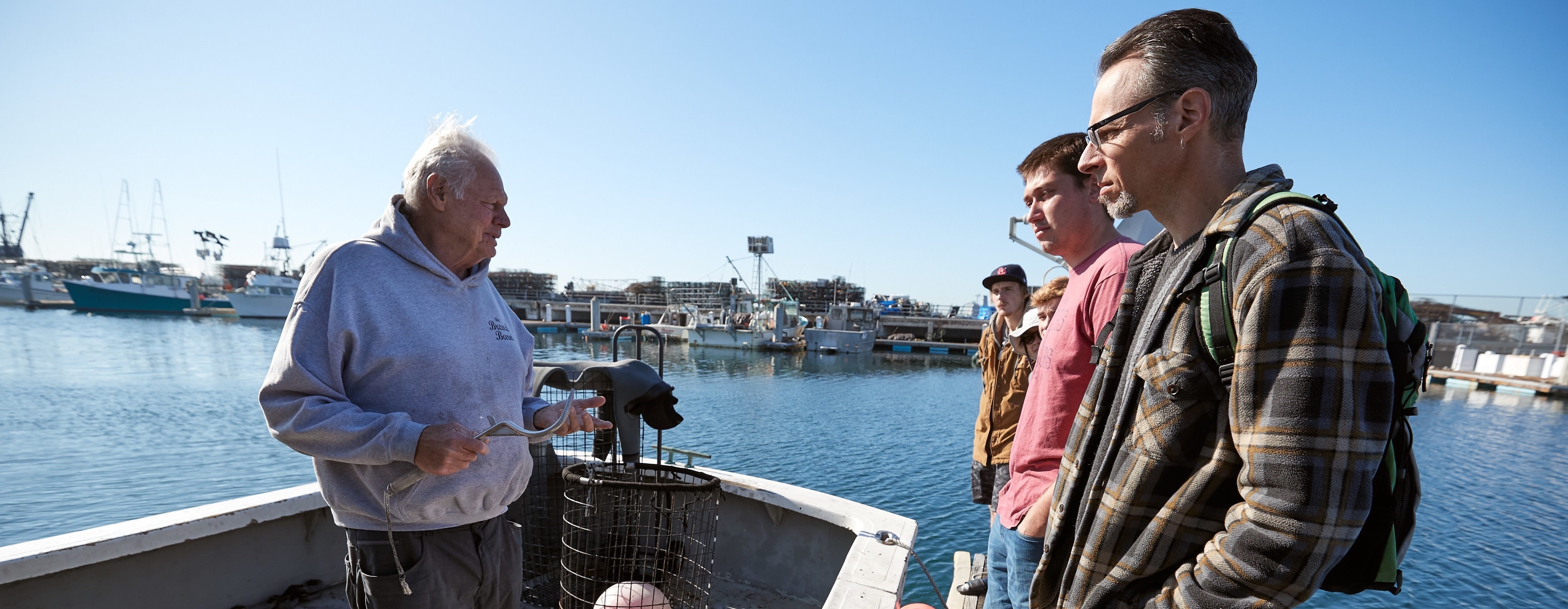A local commercial fisherman standing on his boat talks with the group of apprentices.