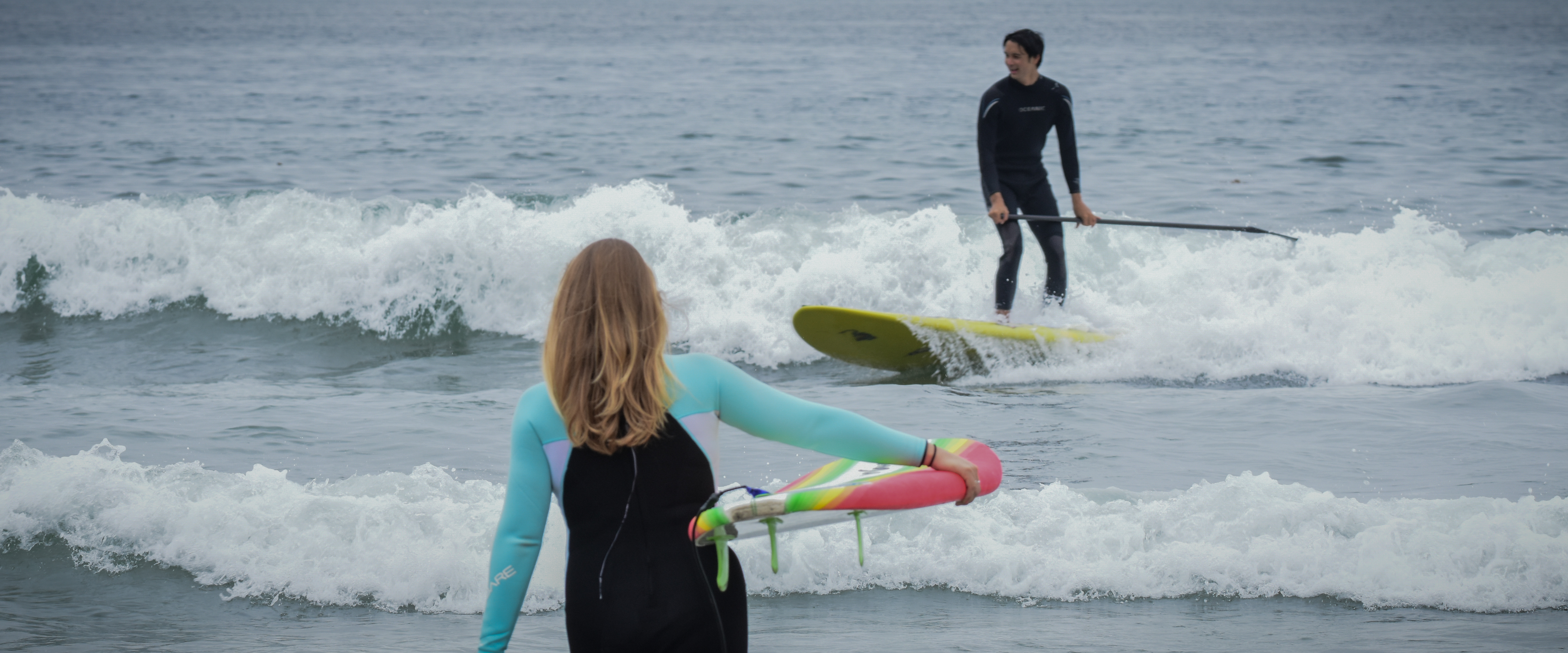 Surfer girl walks into the water carrying a surfboard, while a young man surfs a paddle board on a wave.