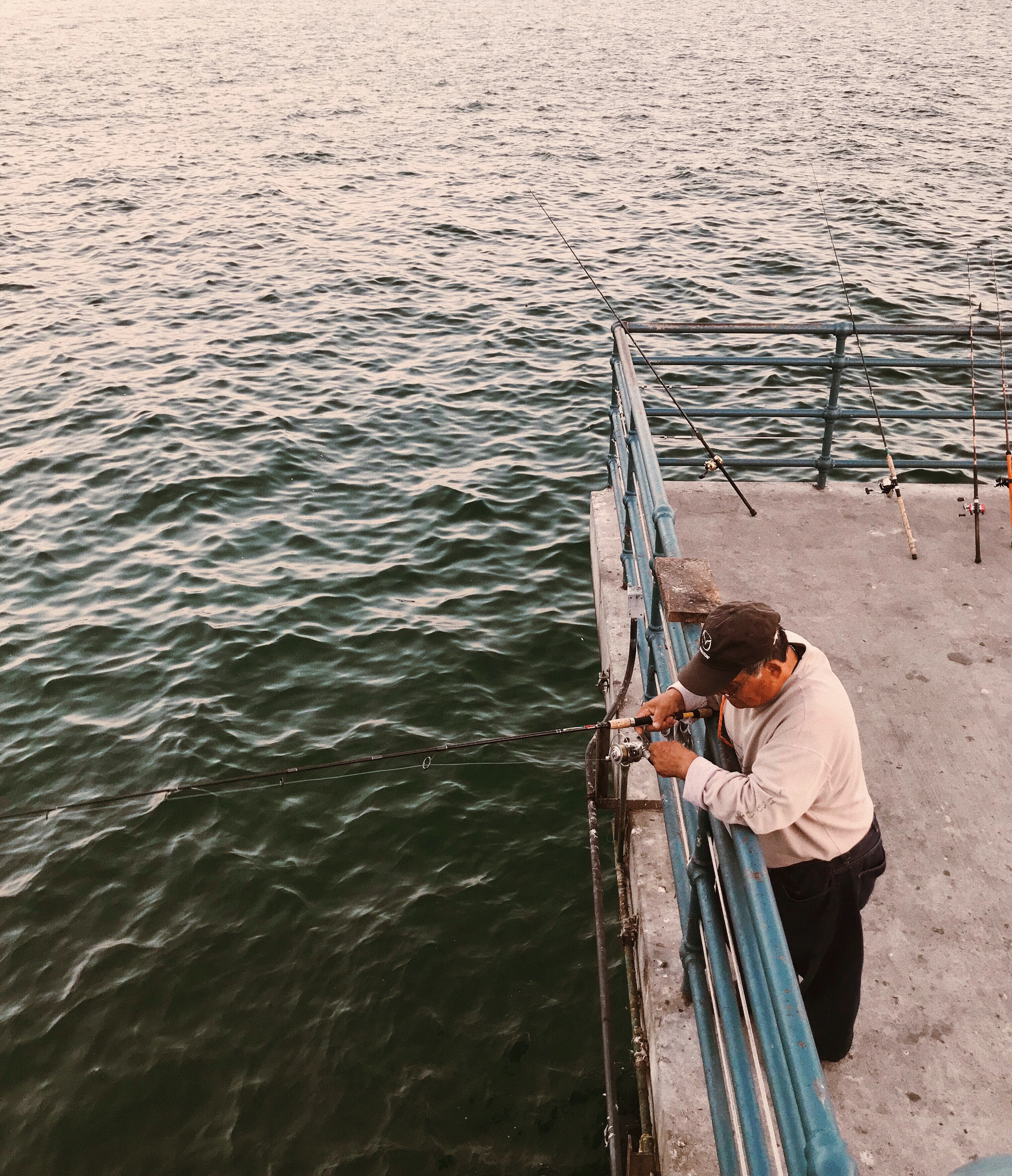 Man fishing off of a pier
