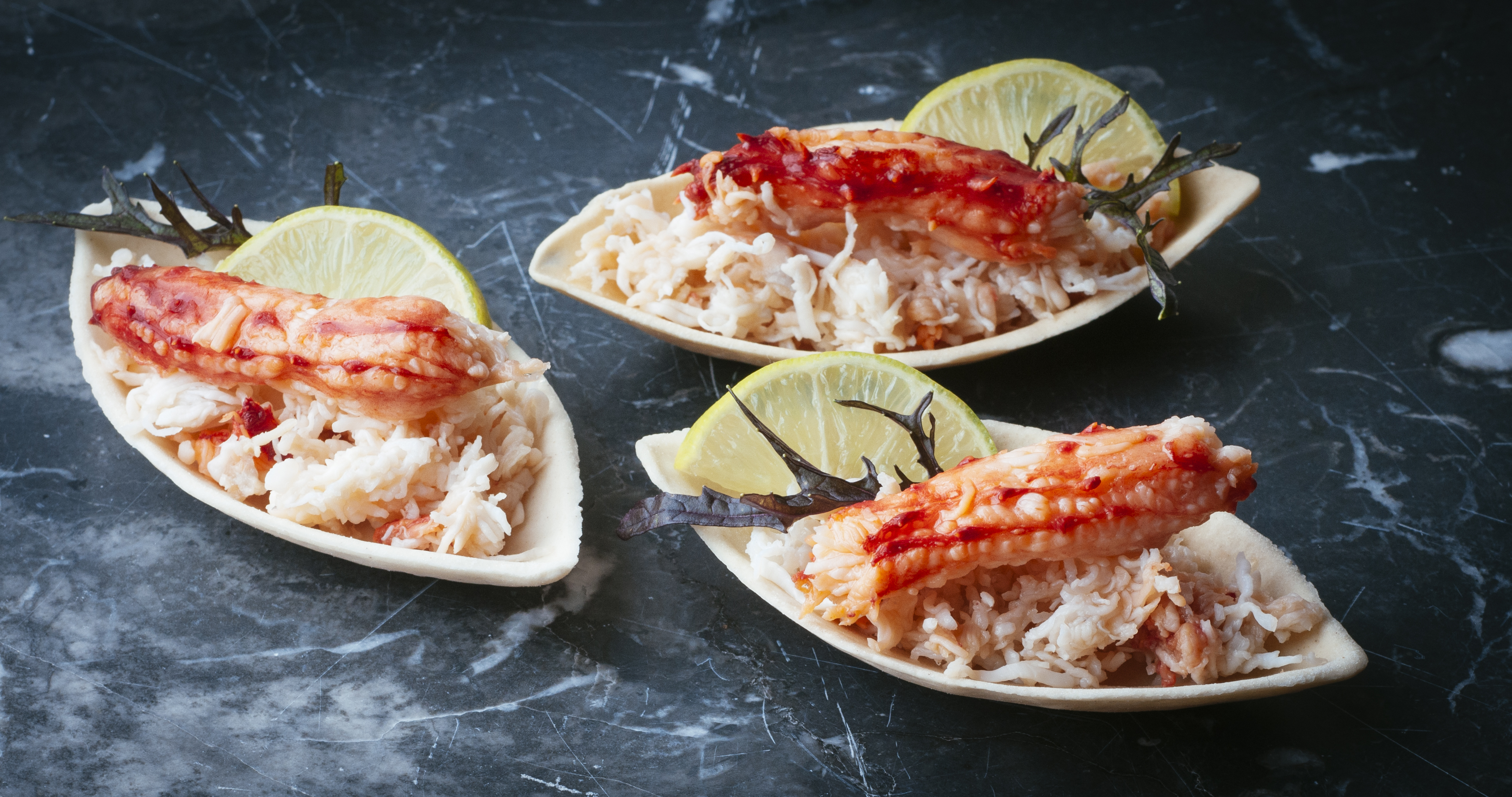 cooked crab laid on decorative platters, garnished with seaweed and lemon