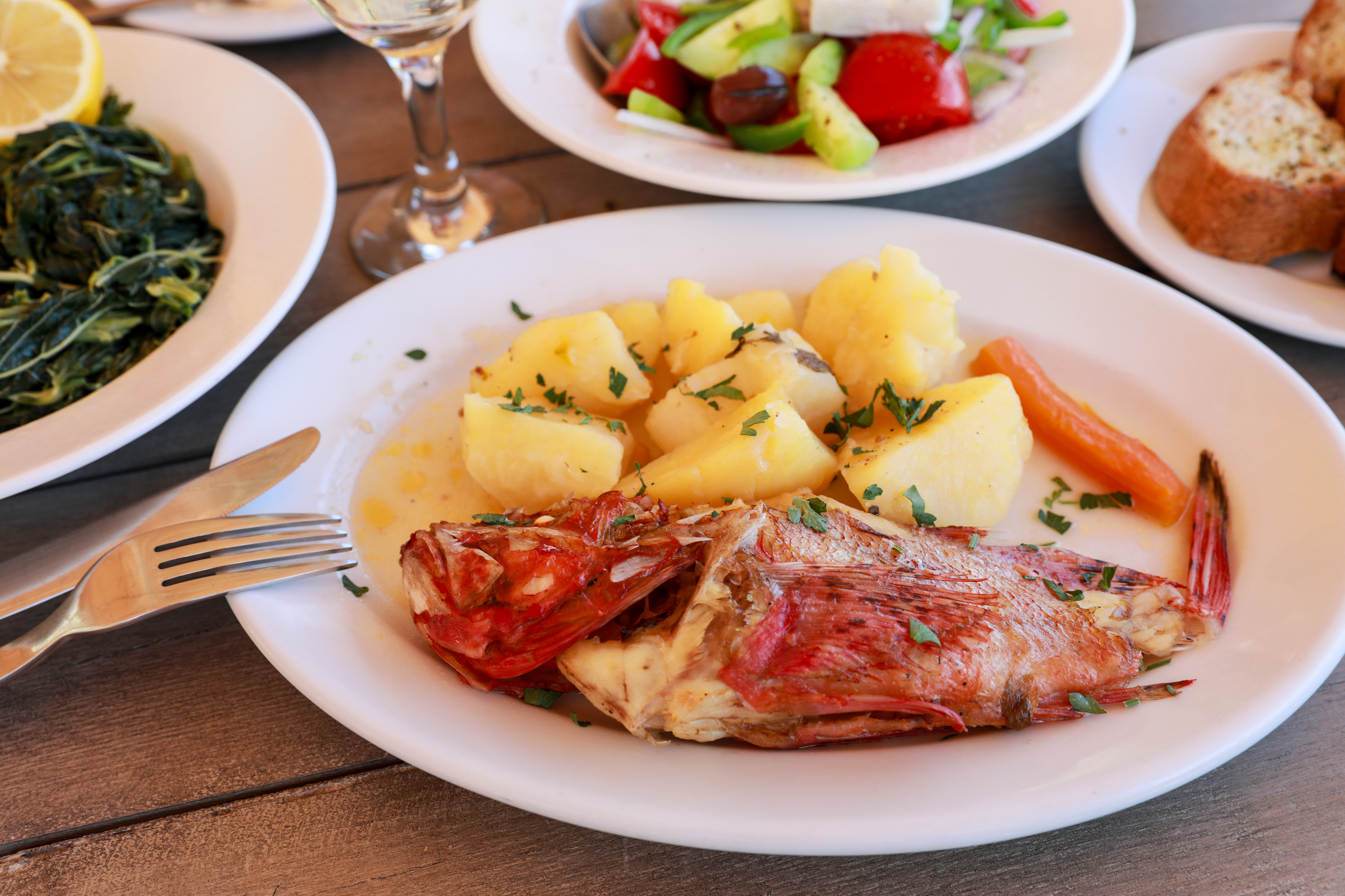 red scorpionfish with potatoes and plates of vegetables and bread