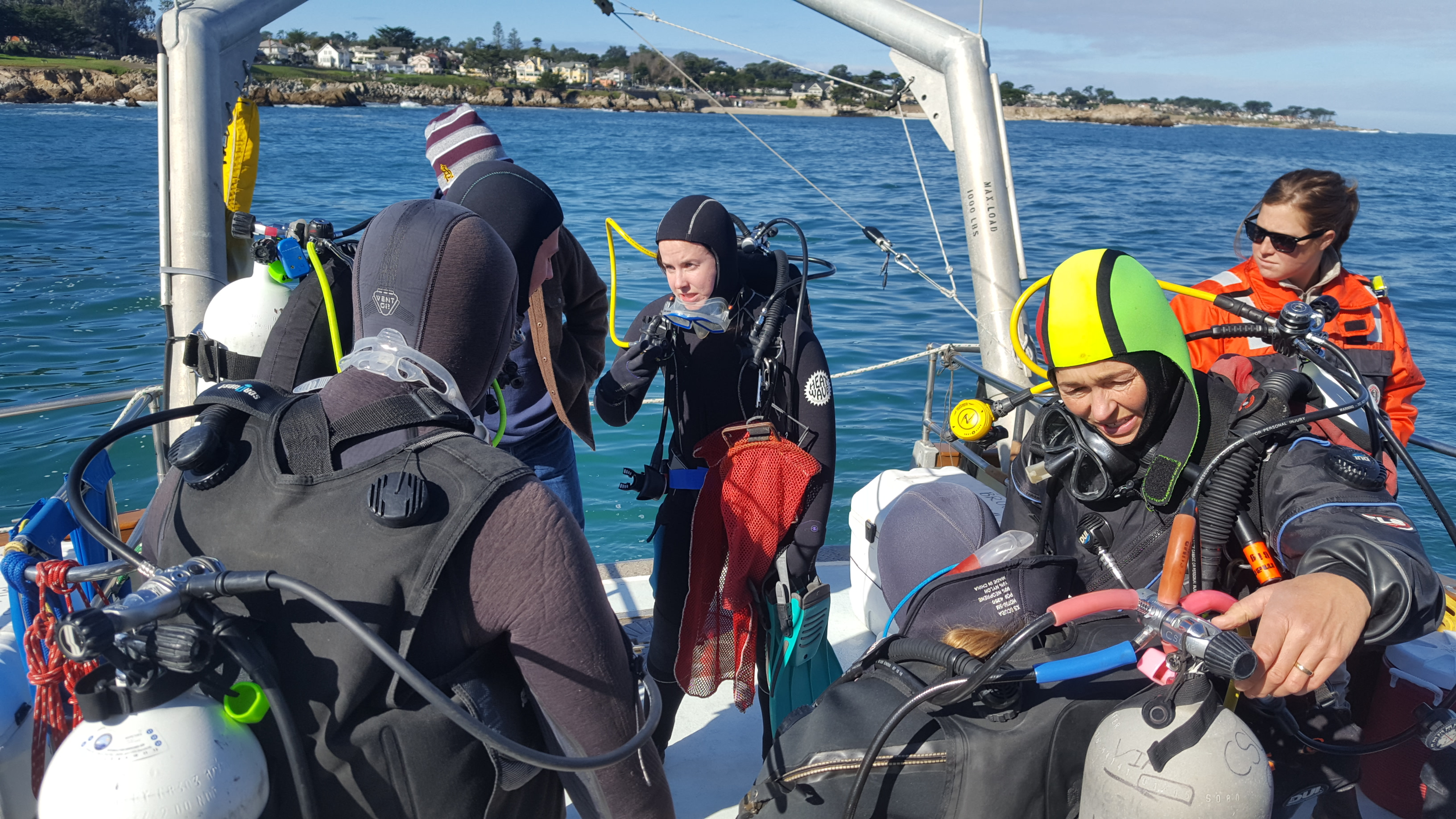 students on a boat preparing to scuba dive to collect urchins from an urchin barren
