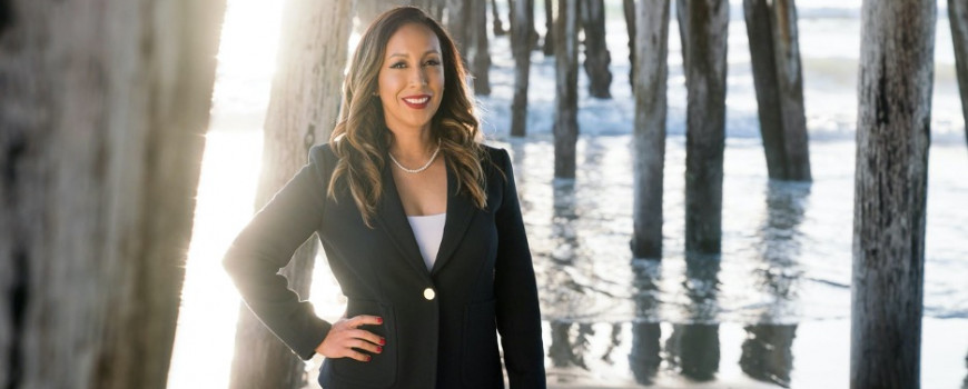 paloma aguirre, in a suit with pier and ocean in background