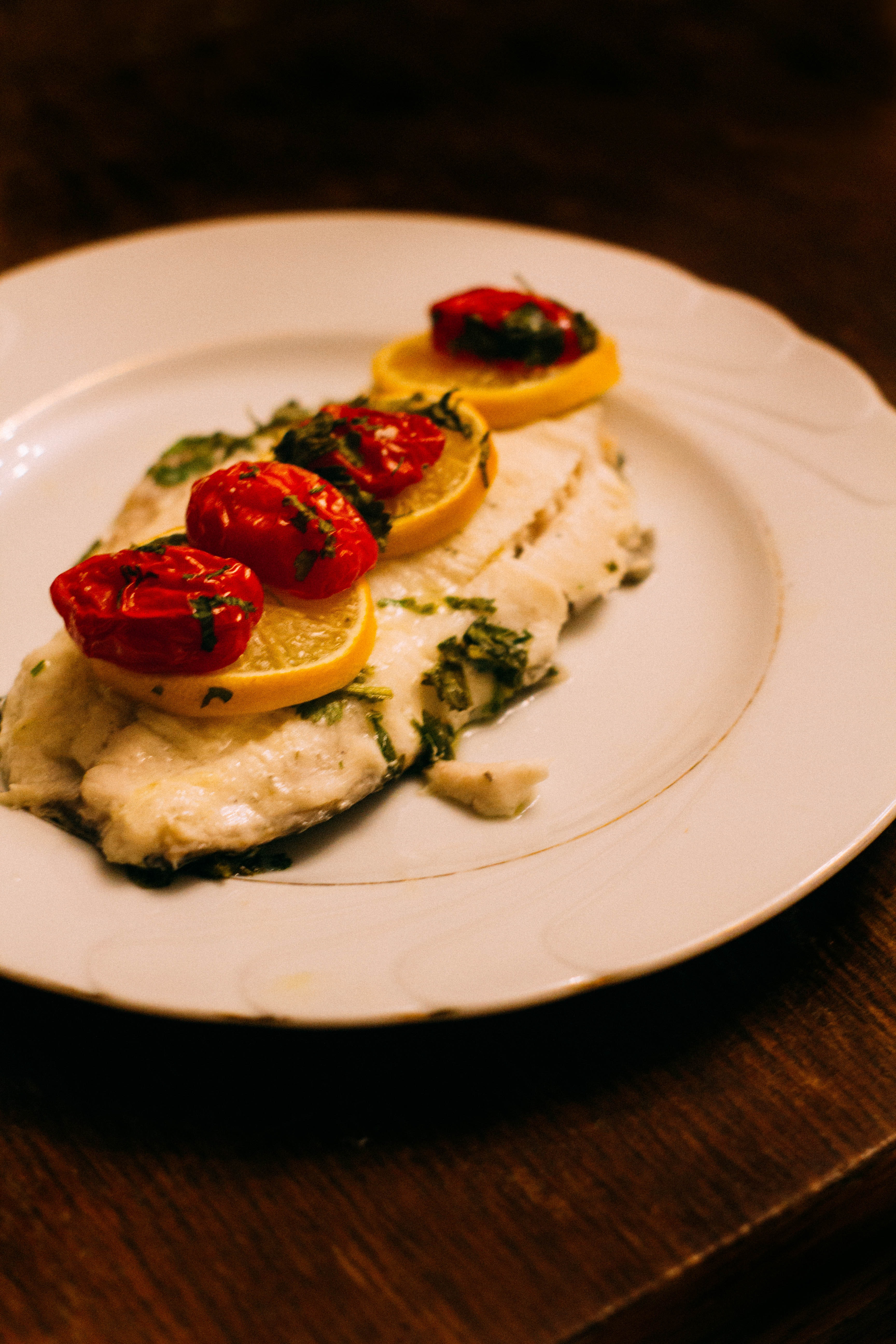 whitefish filet topped with lemon and cherry tomatoes, garnished with greens