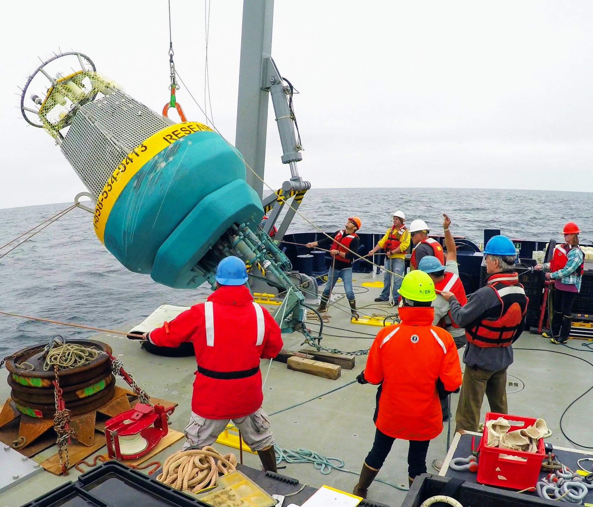 CalCOFI crew lowering a buoy into the ocean