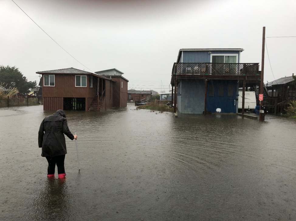 Woman standing by houses and measuring flood water