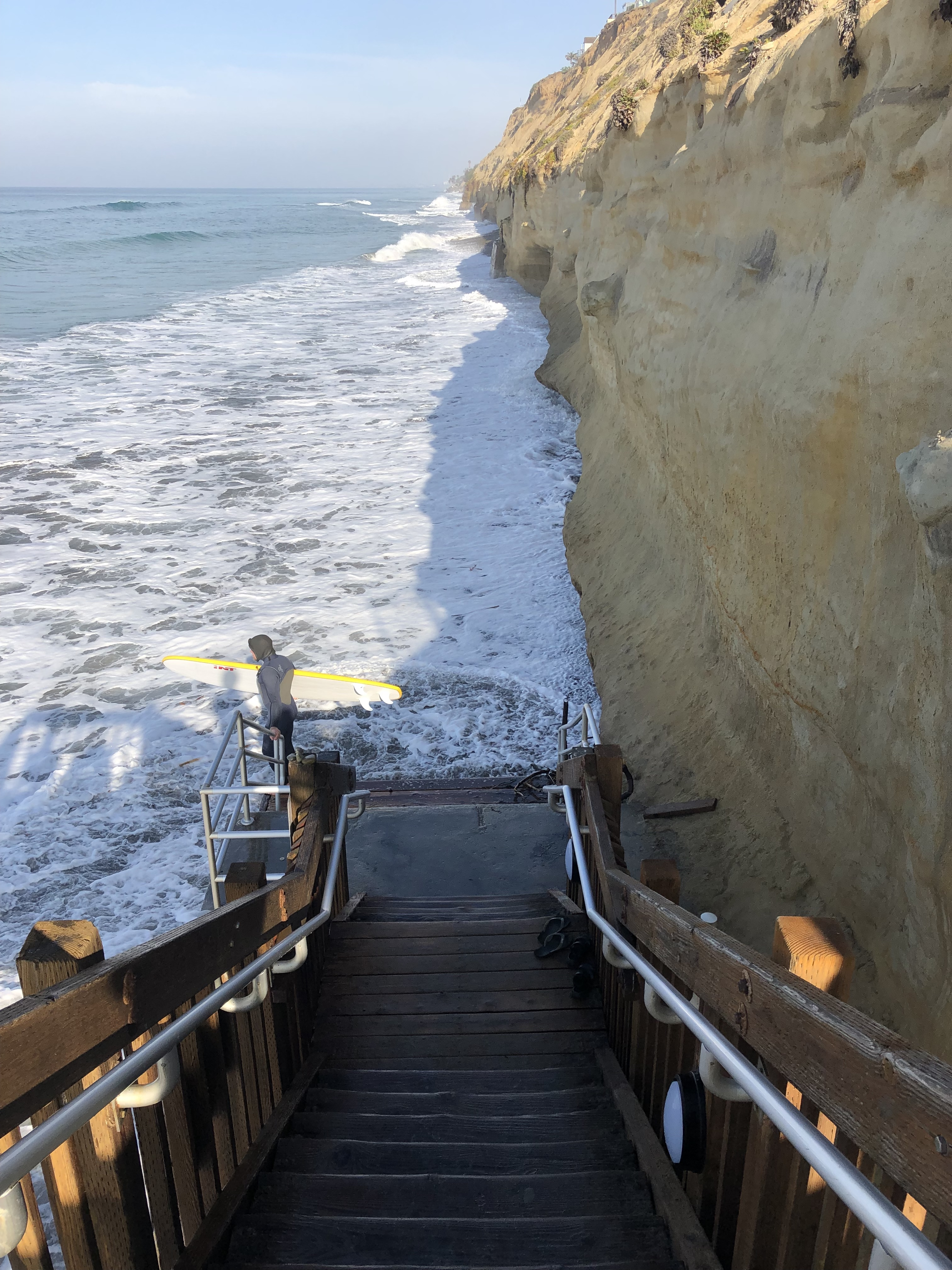 stairs going down to flooded beach from the high tide and swell