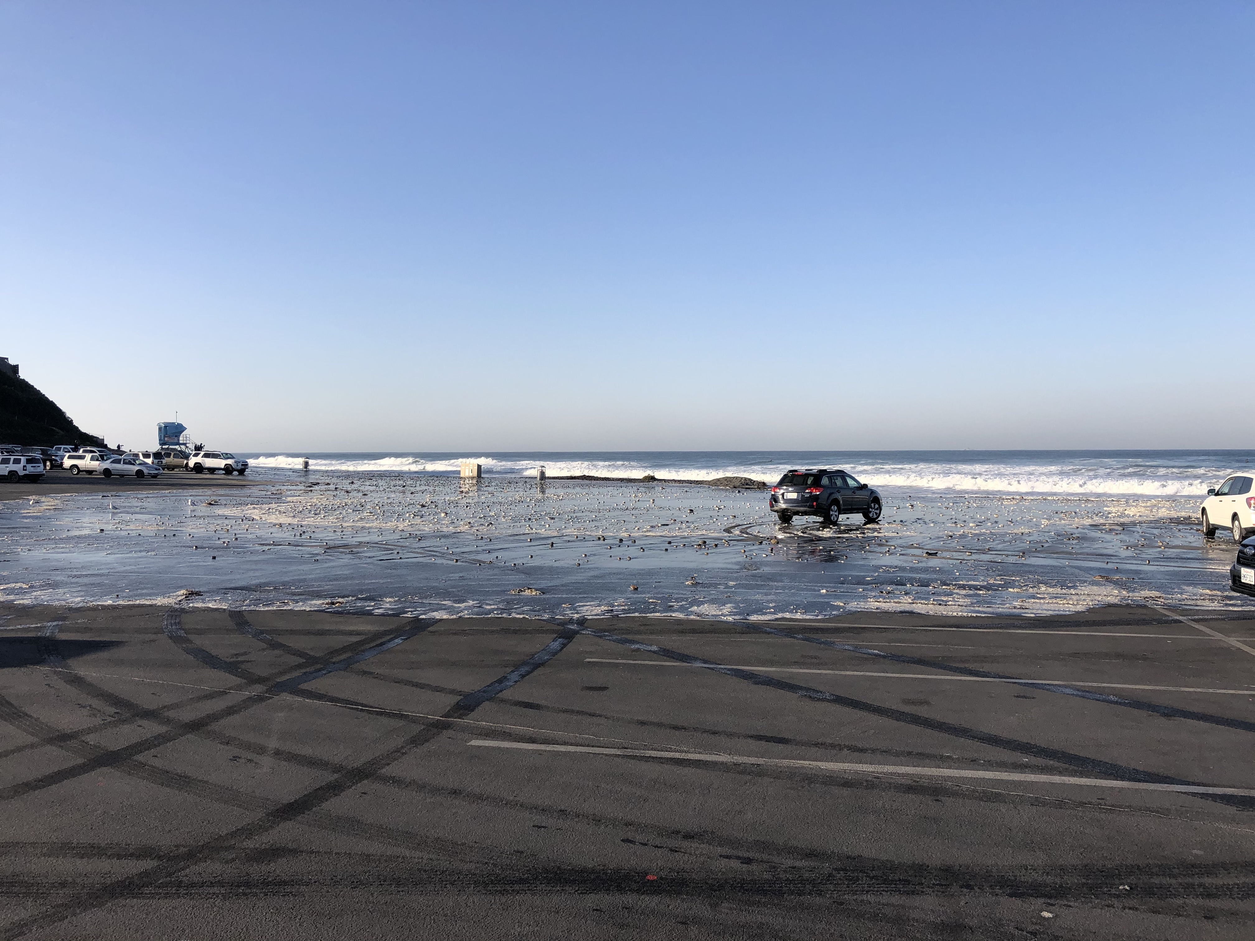 image of flooded beach parking lot caused by combined high tide and moderate swelll